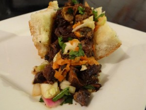 The oxtail sandwich offers picked peppers.