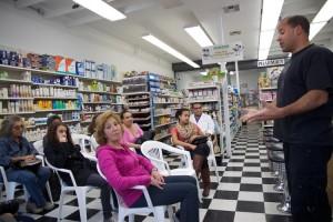 Poet Holden Contreras (standing, on right) leads the pharmacy's poetry slam.