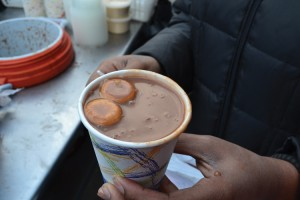 An elated customer receives a cup of <i>habichuelas con dulce</i>.