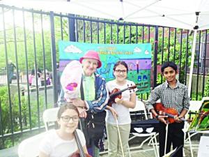 Jeanlee Poggi (con sombrero) del Proyecto de Embellecimiento la calle 181 oeste, de pie con músicos de la orquesta juvenil.